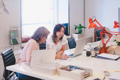Businesswomen working at desk in creative officeの写真素材 [FYI02139700]
