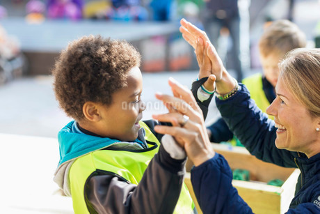 Teacher giving high-five to student outside kindergartenの写真素材 [FYI02139712]