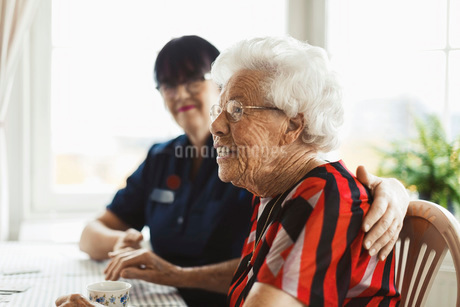 Side view of happy senior woman sitting with caretaker at homeの写真素材 [FYI02139726]