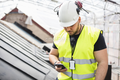 Manual worker using phone while working at construction siteの写真素材 [FYI02139743]