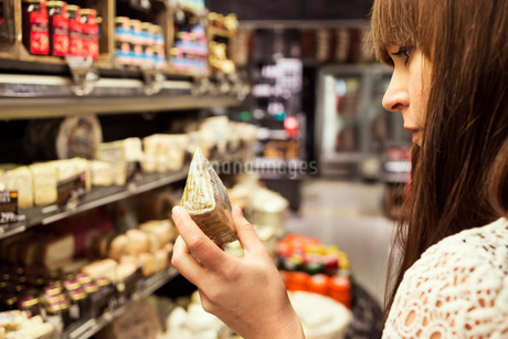 Cropped image of woman analyzing cheese in supermarketの写真素材 [FYI02139750]