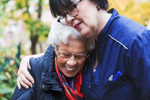 Caretaker embracing senior woman in parkの写真素材 [FYI02139782]