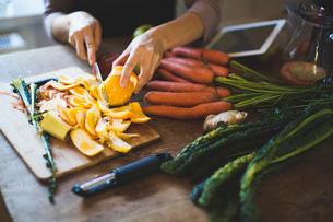 Cropped image of woman peeling orange on cutting boardの写真素材 [FYI02139791]