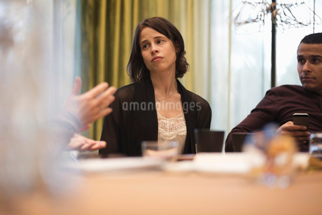 Businessman and woman looking at colleague explaining in meetingの写真素材 [FYI02139892]