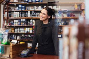 Smiling woman looking away while standing in repair shopの写真素材 [FYI02139893]