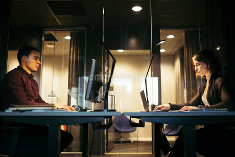Profile view of business people working at desk in officeの写真素材 [FYI02139910]