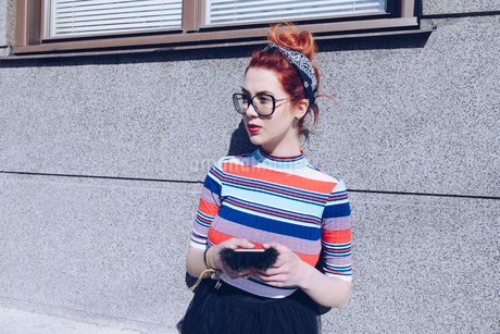 Young female hipster looking away while using mobile phone against wallの写真素材 [FYI02139911]