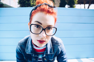 Portrait of redhead young woman wearing eyeglasses while sitting on benchの写真素材 [FYI02139919]