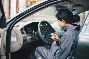 Side view of female mechanic using digital tablet while sitting in carの写真素材 [FYI02139920]