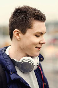 Smiling male university student with headphones around neck outdoorsの写真素材 [FYI02139933]