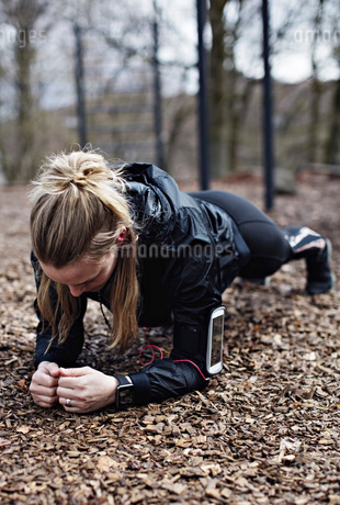 Female athlete performing plank position in forestの写真素材 [FYI02139934]