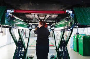 Rear view of female mechanic standing under car on hydraulic liftの写真素材 [FYI02139949]