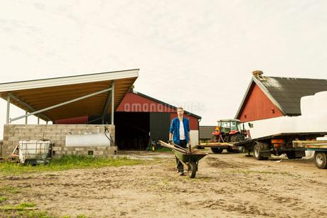Man pushing wheelbarrow on dirt road by tractor against barn at farmの写真素材 [FYI02139950]