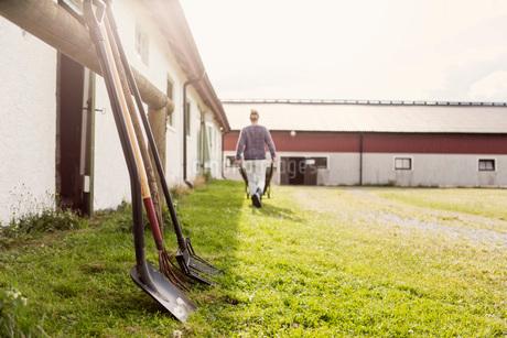 Equipment on grassy field by barn while farmer walking with wheelbarrowの写真素材 [FYI02139951]