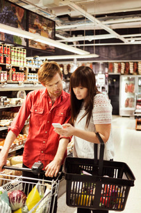 Couple using mobile phone at supermarketの写真素材 [FYI02139994]