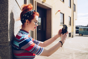 Young female hipster taking selfie while standing against wallの写真素材 [FYI02139995]