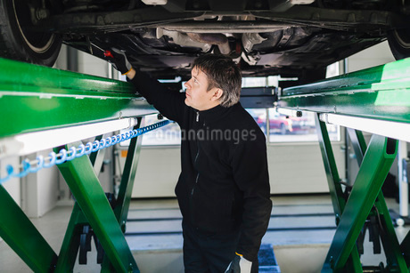 Male mechanic examining car with hammer in auto repair shopの写真素材 [FYI02140014]