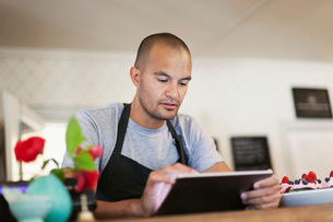 Male owner using digital tablet at cafe counterの写真素材 [FYI02140015]