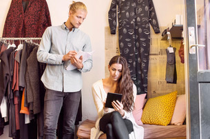 Man looking at woman using digital tablet in clothing storeの写真素材 [FYI02140031]