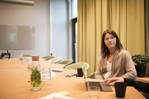 Serious businesswoman sitting with colleague at conference table in board roomの写真素材 [FYI02140038]