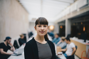 Portrait of female confident computer programmer at office with colleagues working in backgroundの写真素材 [FYI02140080]