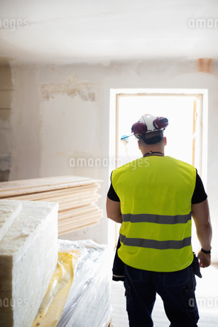 Rear view of man standing in brightly lit room at construction siteの写真素材 [FYI02140104]