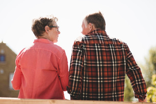 Rear view of senior couple looking at each other while standing against clear skyの写真素材 [FYI02140121]