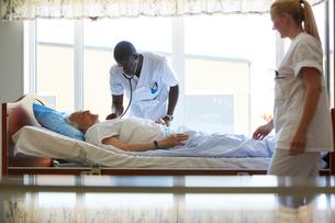 Nurse looking at male colleague examining senior man in hospital wardの写真素材 [FYI02140167]