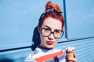 Portrait of redhead young woman holding ice cream cone against mini vanの写真素材 [FYI02140188]