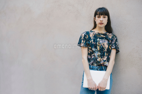 Portrait of confident female computer programmer holding laptop while standing against beige wall inの写真素材 [FYI02140198]