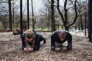 Multi-ethnic couple performing plank exercise at forestの写真素材 [FYI02140219]