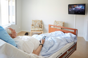 Senior man watching TV while reclining on bed in hospital wardの写真素材 [FYI02140229]