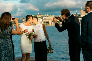 Happy man standing with friends while photographing lesbian couple kissing at weddingの写真素材 [FYI02140234]