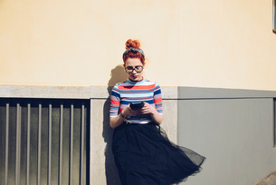 Young female hipster using mobile phone while standing against wallの写真素材 [FYI02140259]
