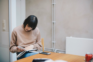 Female computer programmer reading diary in officeの写真素材 [FYI02140349]