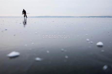 Full length of man ice-skating on frozen lakeの写真素材 [FYI02140402]