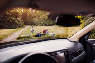 Family on grass at park seen from car windshieldの写真素材 [FYI02140432]