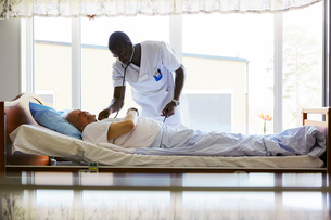 Male nurse examining senior man lying on bed in brightly lit hospitalの写真素材 [FYI02140433]
