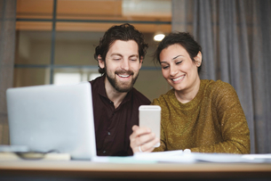 Smiling business colleagues using mobile phone at creative officeの写真素材 [FYI02140434]