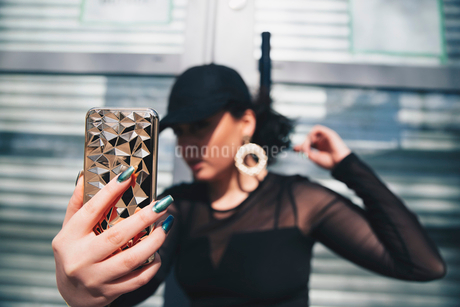 Young woman taking selfie with smart phone against glass doorの写真素材 [FYI02140471]