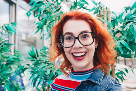 Portrait of smiling redhead young woman against plantの写真素材 [FYI02140473]