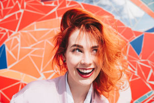 Smiling redhead young woman against mosaic wallの写真素材 [FYI02140476]