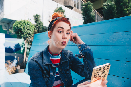 Redhead young woman taking selfie with mobile phone while sitting on benchの写真素材 [FYI02140479]