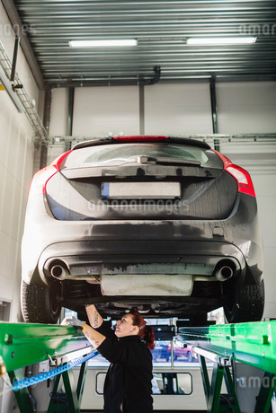 Side view of female mechanic repairing car on hydraulic liftの写真素材 [FYI02140482]