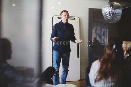 Mature businessman giving presentation to colleagues in board room seen from glassの写真素材 [FYI02140511]