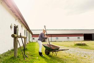 Female farmer removing work tools from wheelbarrow at farmの写真素材 [FYI02140516]