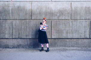 Young woman looking at mobile phone while applying lipstick against wallの写真素材 [FYI02140521]