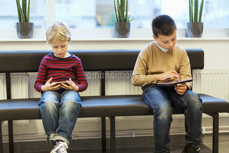 Boys using technologies while waiting at orthopedic clinicの写真素材 [FYI02140536]