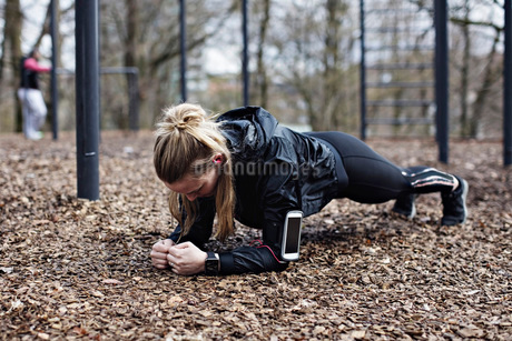 Full length of female athlete performing plank position in forestの写真素材 [FYI02140553]