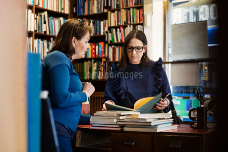 Female customer discussing with librarian standing in bookstoreの写真素材 [FYI02140745]